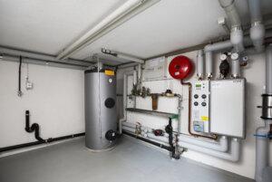 Einfach und platzsparend: Wo früher ein grosser Öltank stand, überträgt heute eine kleine Übergabestation mit Wärmetauscher (rechts im Bild) die Wärme des Fernwärmenetzes in den Heizkreislauf des Hauses. – Bild: Gabi Vogt Download